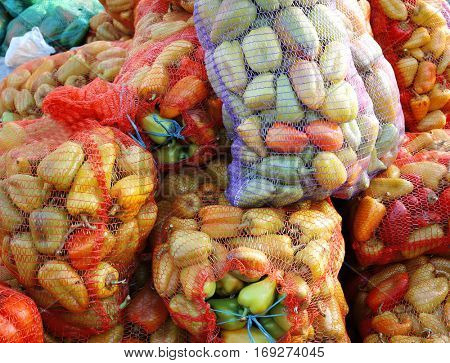 Fresh sweet pepper in mesh bags on market
