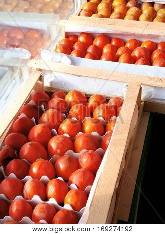 Fresh persimmons in wooden crate on market