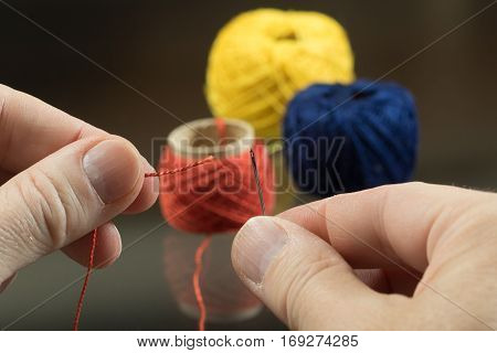 Tailor fingers is threading a needle on golden background