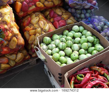 Fresh vegetables in cardboard boxes and mesh bags on market
