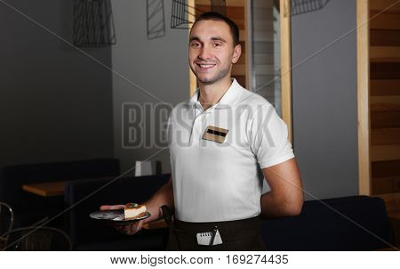 Young handsome waiter holding plate with delicious cake in a restaurant