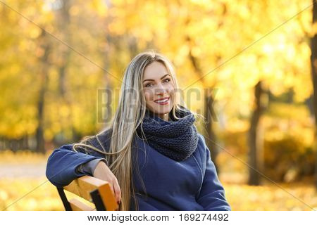 Beautiful young woman sitting on bench in autumn park