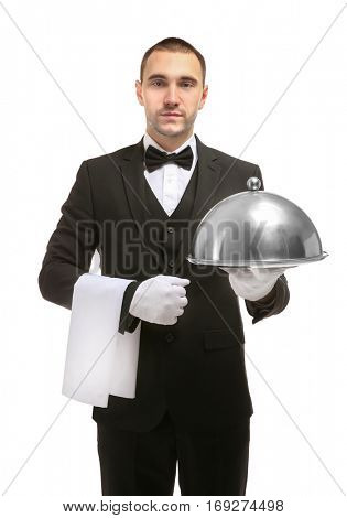 Handsome waiter holding serving tray with metal cloche and napkin on white background