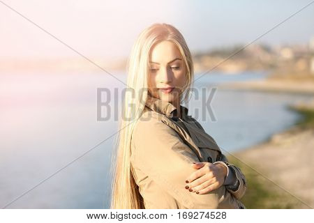 Beautiful young woman near river on sunny autumn day