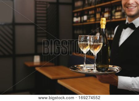 Young handsome waiter holding tray with wine glasses in the restaurant