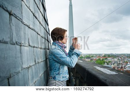 Girl making a photo of a city. Female tourist looking at view taking snapshots