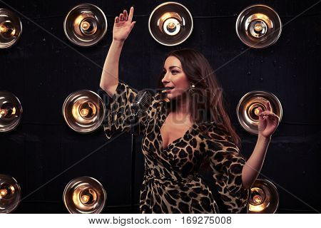 Mid shot of affecting brunette in a sexy leopard dress with hands up looking away from the camera. Good-looking woman in chiffon leopard dress with evening makeup in eveningwear