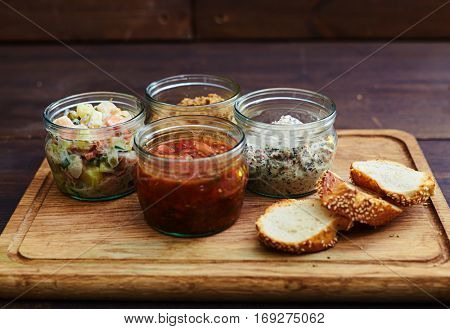 Close-up of a mix of homemade salads in jars served with crusty bread. Dressed salad for lunch. Lunchtime food. The concept of nutritious dinner