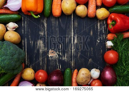 Top view of vegetables over black flat layout.  Clean and healthy vegetables forming a frame isolated over background