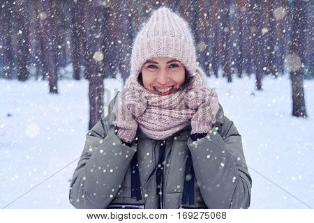 Close-up of woman with amazing eyes looking at the camera. Standing in the forest. Holding a knitted scarf, wearing a nice cap. Winter concept