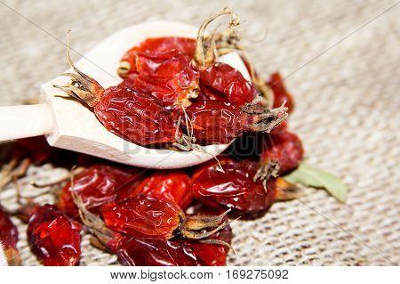 Dried rosehip berries in a wooden spoon