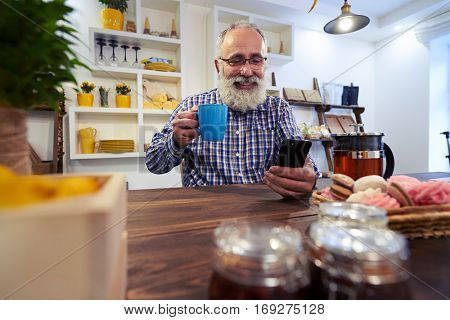 Close-up of happy young man who is using a smart phone in a kitchen at home. Young man sitting at a table in the kitchen with a cup of tea watching video