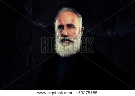 A mid shot of handsome elderly bearded man looking wisely in camera. Wearing warm black sweater