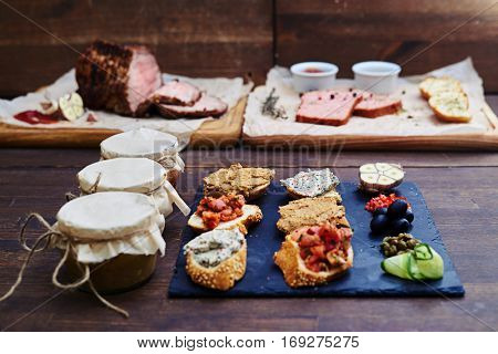 Close-up of an assortment of different kinds of food, gastronomic variety. Appetizer canapes of baguette with different combinations of toppings. Succulent baked meat with garnish on a cutting board