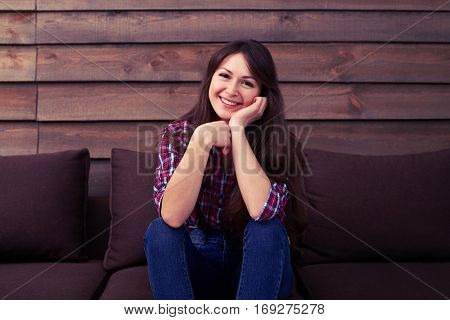 A mid shot of pretty smiling girl wearing jeans and check shirt. Female sitting on the sofa