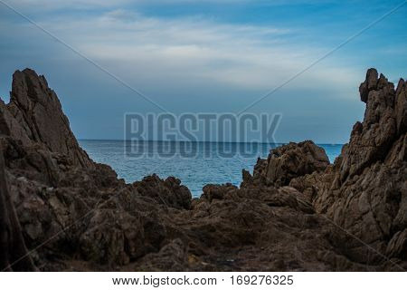 Closeup large formation of rocks on shoreline between beach and sea against blue sky and white clouds