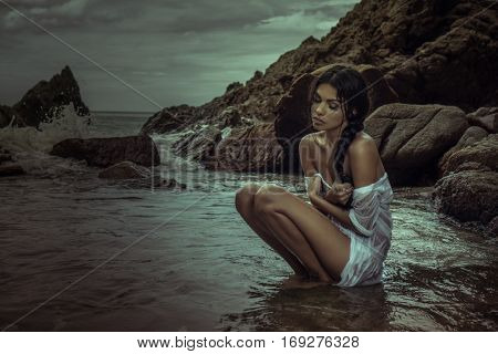 Romantic brunette beauty wearing white wet shirt sitting in the water between rocks over sea and cloudy sky background
