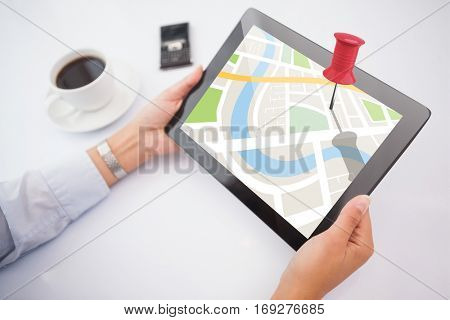 Man using tablet pc against close-up of red pushpin