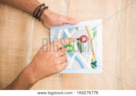 Colorful navigation pointers with various representations on map against hand pointing blank screen tablet Digital image of colorful navigation pointers with various representations on map