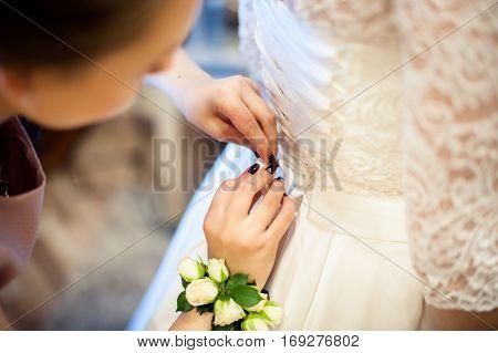 Bride Fees. Bridesmaid Helps To Fasten A Corset