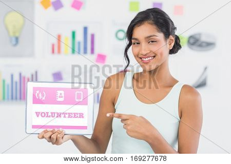 Smiling businesswoman pointing at digital tablet in creative office against blue volunteer