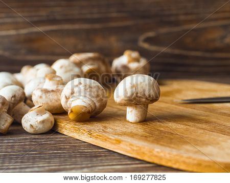 Fresh organic champignon mushrooms on chopping board with knife.