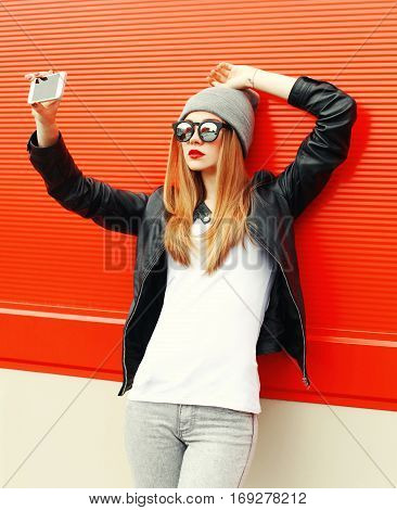 Fashion Girl Taking Self-portrait On Smartphone In City Over Red Background