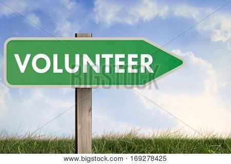 Word volunteer against field of grass under blue sky
