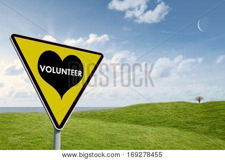 Volunteer heart against green field under blue sky