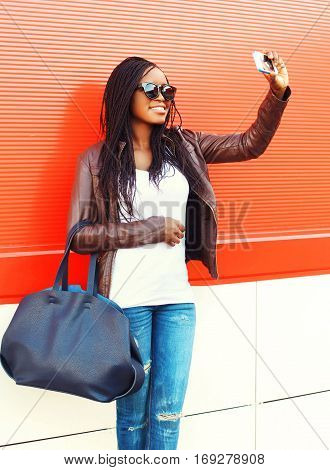 Fashion Smiling African Woman Taking Self-portrait Picture On Smartphone In City Over Red Background