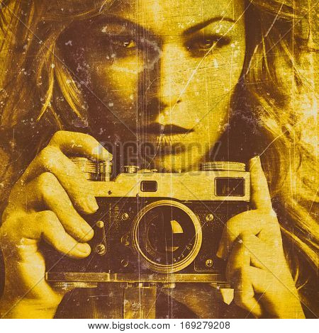 Beautiful woman taking photos with retro film camera. Close up. Old grungy texture. Golden concrete wall