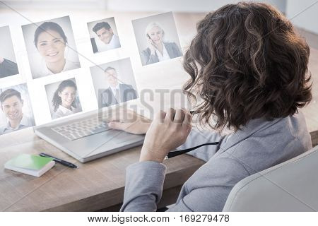Businesswoman using laptop at desk in creative office against portrait of business people