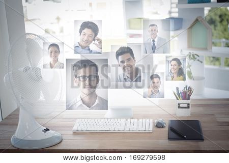 Portrait of business people against sticky notes on computer monitor by electric fan