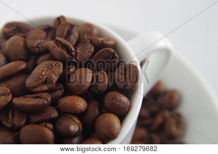 fresh roasted coffee beans in a white coffee cup