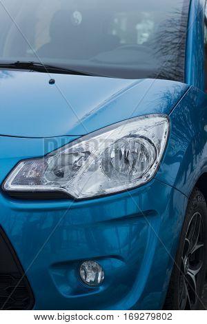 Car white headlight on passenger blue car