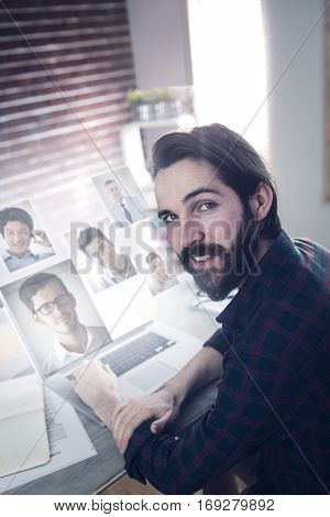 Portrait of business people against portrait of smiling graphic designer using laptop