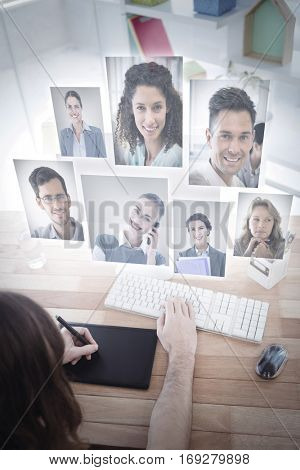 Portrait of business people against hipster with graphics tablet working at computer desk