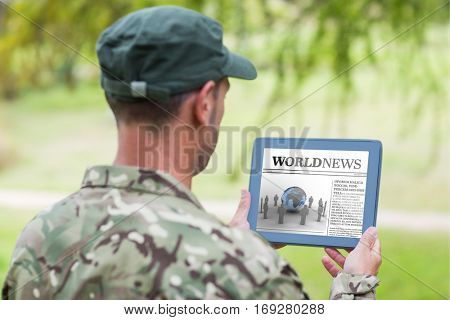 Army man using tablet against international newspaper