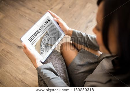 Business newspaper against businesswoman using tablet