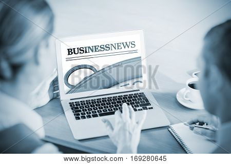 Close up on newspaper against business people working together while using laptop