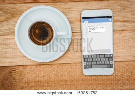 Smartphone text messaging against above view of a coffee and a smartphone