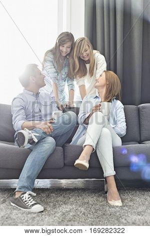 Happy parents with daughters spending quality time in living room