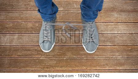 Low section of man with shoelaces tied together against wooden planks background