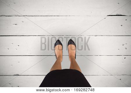 Businesswomans feet against white wood