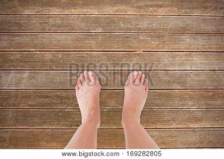 Feet against wooden planks background