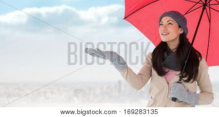 Smiling brunette feeling the rain against balcony overlooking city