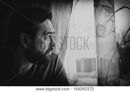 Pensive man looking through the window. Black and white portrait