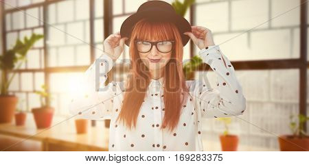 Attractive smiling hipster woman with hat against a line of green plants