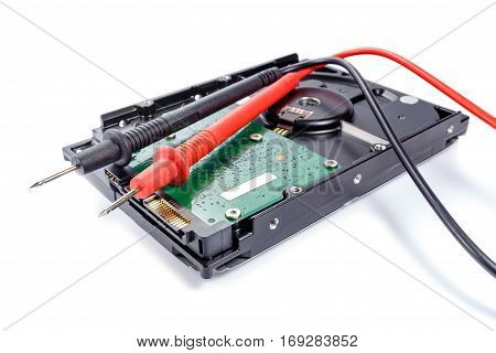 Hard disk drive with multimeter probes on a white background
