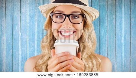 Gorgeous smiling blonde hipster with take-away cup against wooden planks